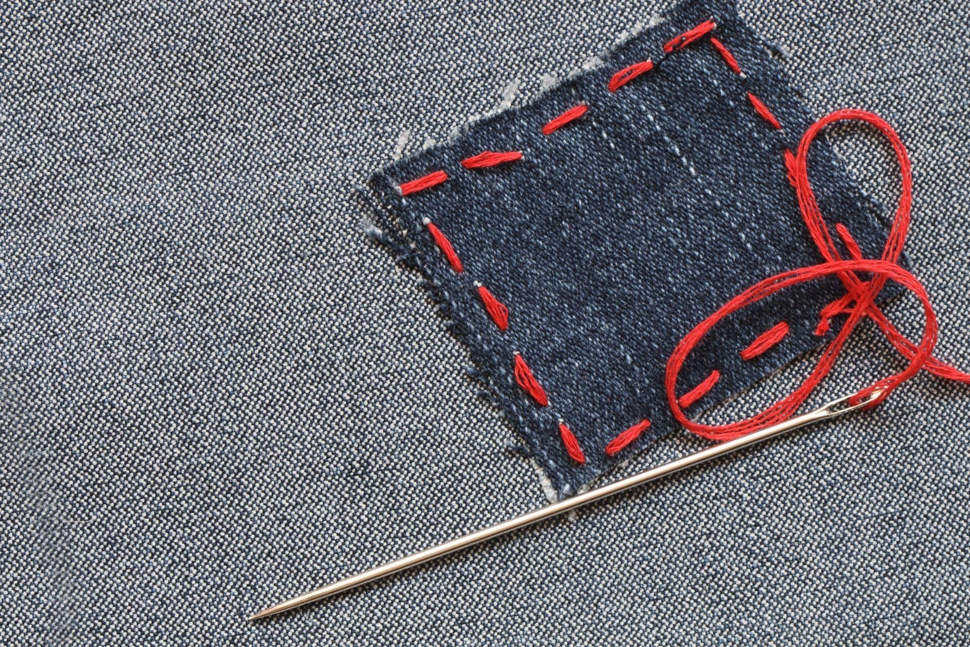 tkanina dżinsowa przeszyta czerwoną nicią